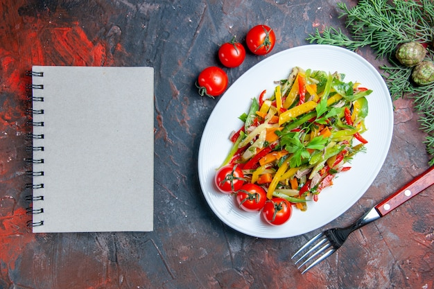 Top view vegetable salad on oval plate fork cherry tomatoes notebook on dark red table