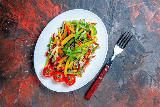 Vista dall'alto insalata di verdure sulla forcella piatto ovale sul tavolo rosso scuro