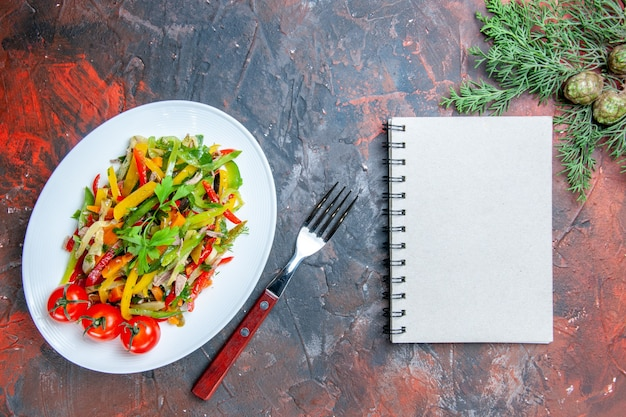 Top view vegetable salad on oval plate fork notebook pine branches on dark red table