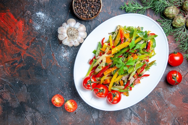 Top view vegetable salad on oval plate garlic cherry tomatoes black pepper on dark red table