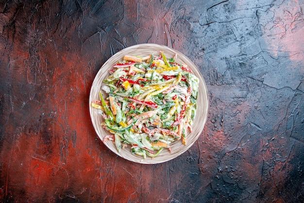 Vista dall'alto insalata di verdure sulla piastra sullo spazio libero tavolo rosso scuro