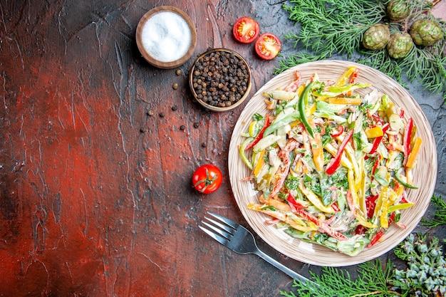 Vista dall'alto insalata di verdure su piastra forcella sale e pepe nero tamatoes sul tavolo rosso scuro con spazio di copia