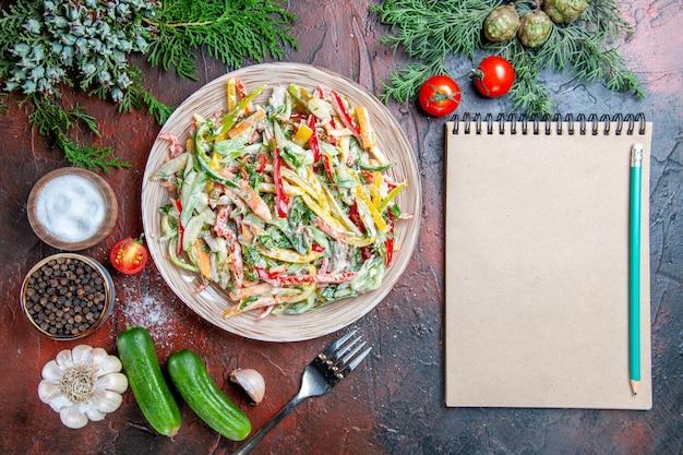 Vista dall'alto insalata di verdure sulla piastra forcella pomodori rami di pino cetrioli aglio matita sul blocco note sul tavolo rosso scuro