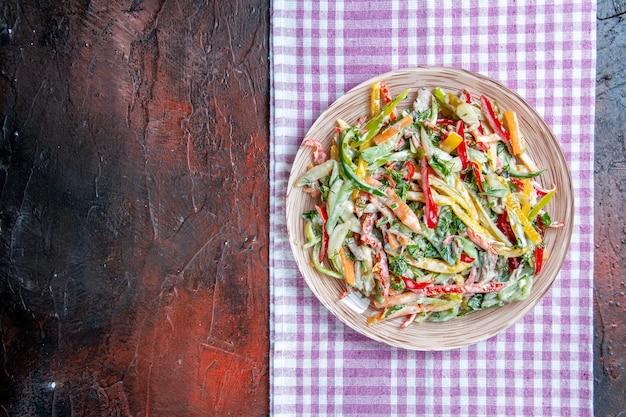 Vista dall'alto insalata di verdure sul piatto sulla tovaglia sul posto di copia tavolo rosso scuro