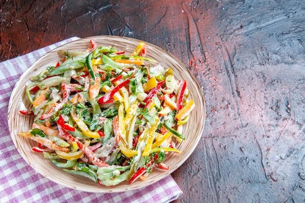 Vista dall'alto di insalata di verdure sul piatto sulla tovaglia sullo spazio libero tavolo rosso scuro