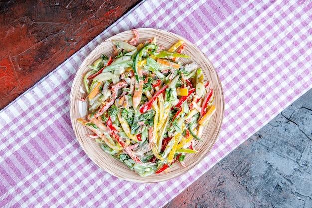 Vista dall'alto di insalata di verdure sul piatto sulla tovaglia sul tavolo rosso scuro