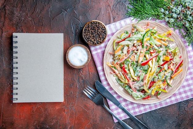 Vista dall'alto insalata di verdure sul piatto sulla tovaglia forchetta e coltello sale e pepe nero un taccuino sul tavolo rosso scuro