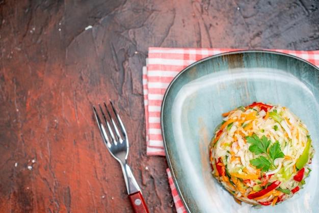 Insalata di verdure vista dall'alto piatto interno a forma rotonda sul tavolo scuro