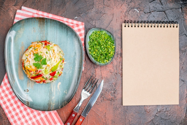 暗いテーブルの上のプレートの内側に丸い形の野菜サラダの上面図