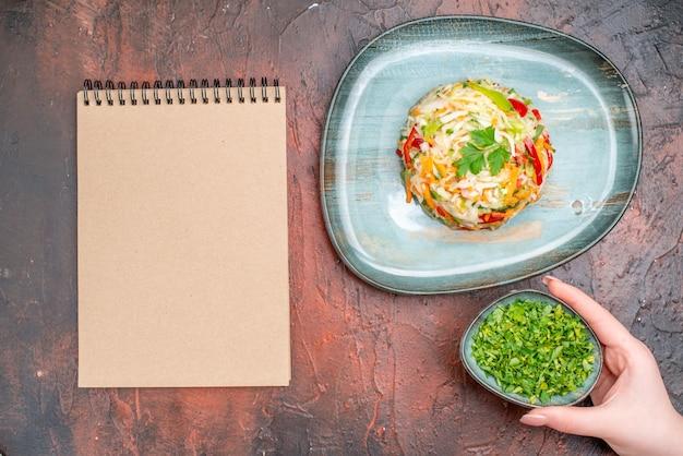 暗いテーブルの上に緑のあるプレートの内側に丸い形の野菜サラダの上面図