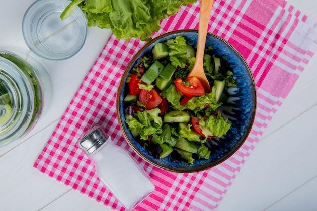 Vista superiore di insalata e sale di verdure sul panno del plaid con acqua della disintossicazione e lattuga su legno