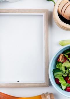 La vista superiore di insalata di verdure con pepe nero nel cruhser dell'aglio ha fuso il burro e la struttura su superficie bianca con lo spazio della copia