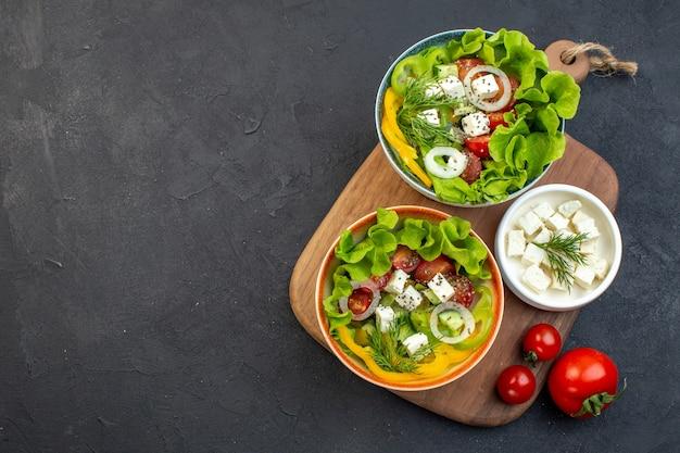 어두운 배경에 치즈 오이와 토마토와 상위 뷰 야채 샐러드