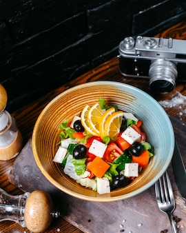 Top view of vegetable salad with feta cheese lemon slices and black olives in a bowl on a wooden table