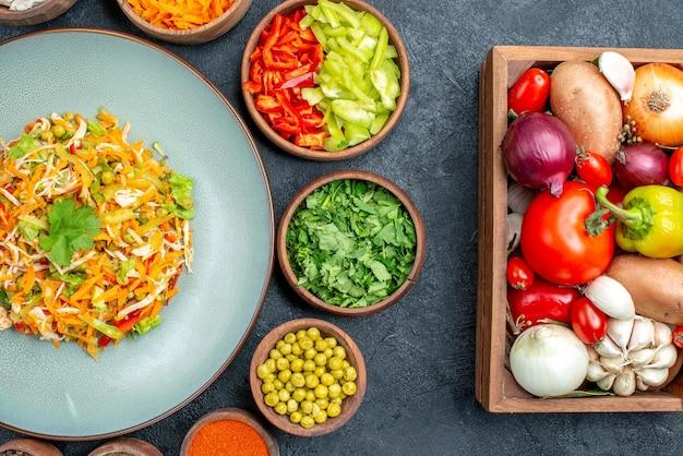 Вид сверху овощной салат со свежими овощами на темном салате из спелых блюд