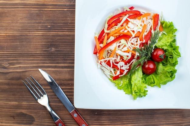 Vista dall'alto di insalata di verdure con insalata verde e cavolo all'interno della piastra sulla superficie marrone