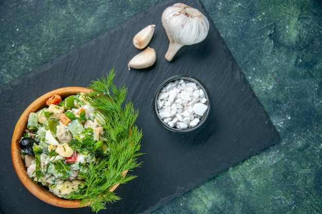 Top view vegetable salad with greens and garlic on dark blue background