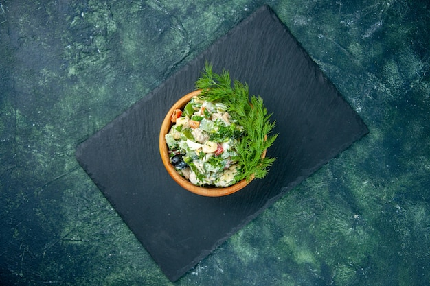 Top view vegetable salad with greens inside little pot on dark-blue background