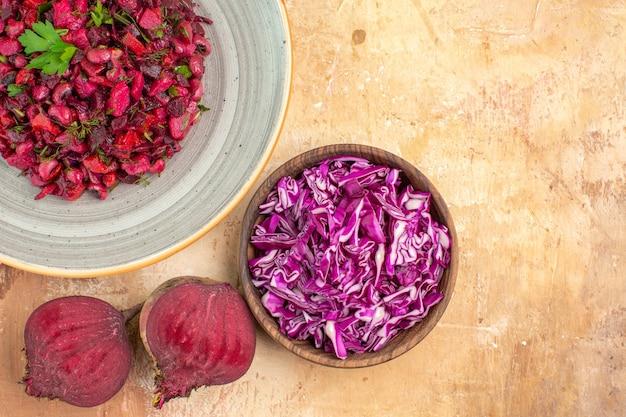 空きスペースのある木製のテーブルの上にビートの根と刻んだキャベツのボウルとパセリの葉とトップビュー野菜サラダ
