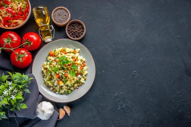 어두운 배경에 빨간 토마토와 조미료를 곁들인 상위 뷰 야채 샐러드 다이어트 수평 점심 식사 빵 요리 건강