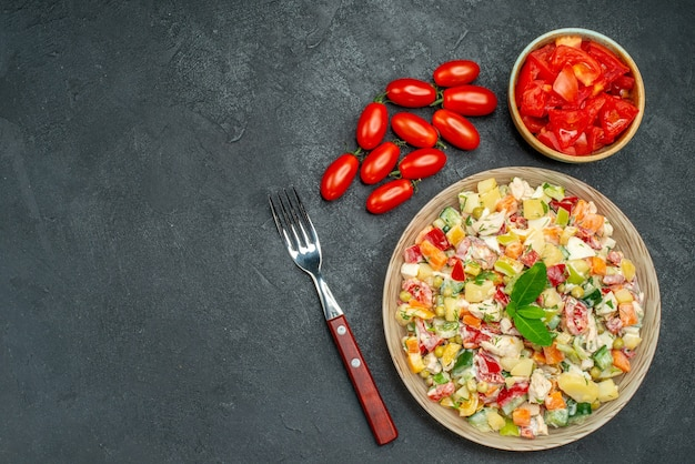 Top view of vegetable salad with tomatoes and fork on dark grey background