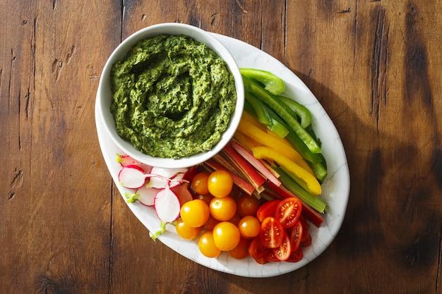 Top view vegetable snacks pesto sauce served plate