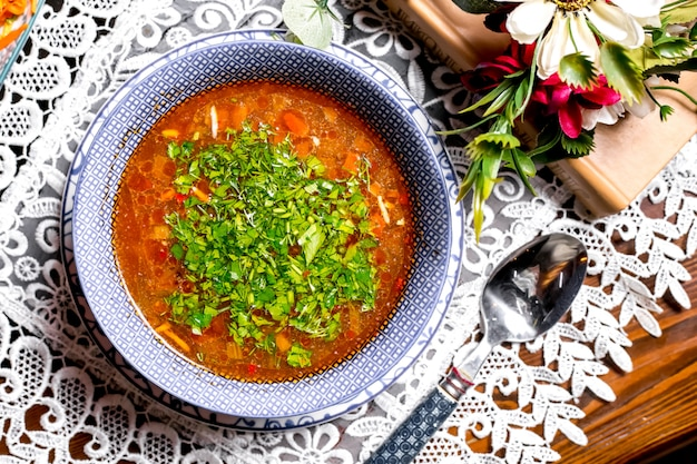 Top view of vegetable soup bowl garnished with herbs