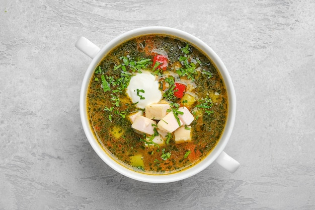 Top view of vegetable soup with chicken fillet and sour cream