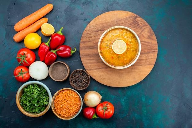 Vista dall'alto di zuppa di verdure con verdure fresche e condimenti sulla superficie blu scuro