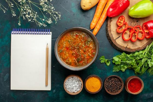 Zuppa di verdure vista dall'alto con verdure fresche e condimenti su una zuppa di verdure pasto ingrediente scrivania verde scuro
