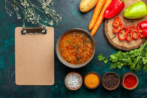 Zuppa di verdure vista dall'alto con verdure fresche e condimenti su zuppa di verdure cibo pasto ingrediente superficie verde scuro