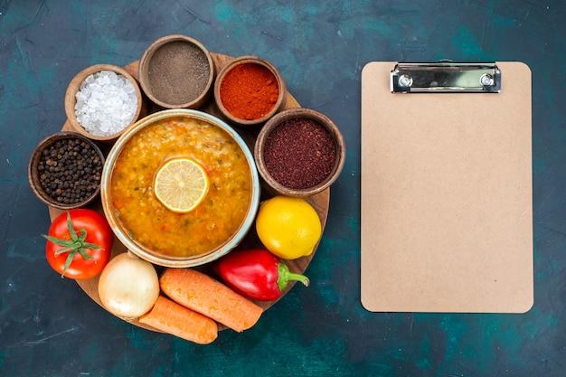 Vista dall'alto di zuppa di verdure con limone insieme a condimenti e verdure fresche sulla superficie blu scuro