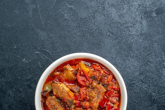 Zuppa di verdure vista dall'alto con carne all'interno del piatto su grigio scuro