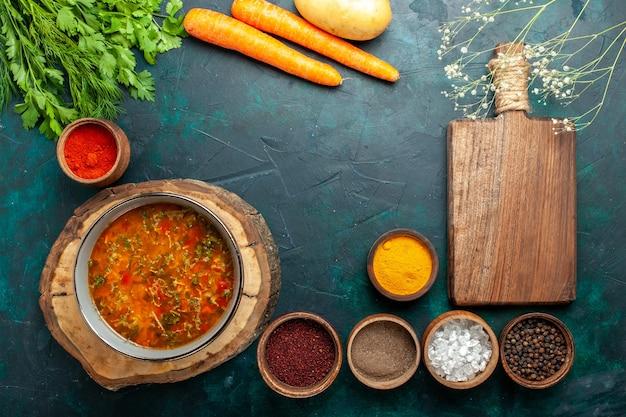 濃い緑色の机の上に調味料を入れた上面野菜スープ材料スープ食事食品野菜