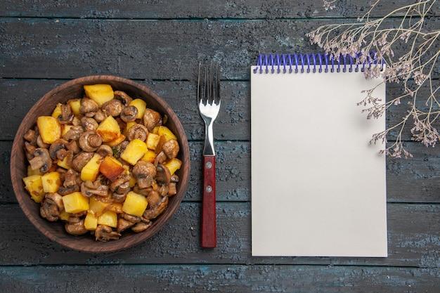 フォークノートと暗いテーブルの枝の横にあるボウルにキノコジャガイモとキノコが入った上面図野菜