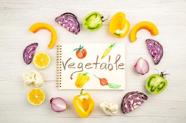 上面図メモ帳に書かれた野菜カット野菜赤キャベツ緑トマトカボチャ赤玉ねぎ黄色ピーマンcaulifowerレモン白いテーブルに