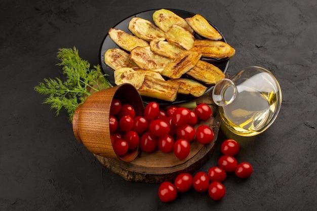 Овощи сверху вместе с приготовленным баклажаном на темном фоне