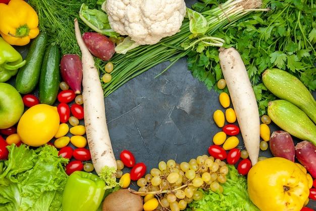 Вид сверху овощи и фрукты помидоры черри кумкуат салат айва виноград лимон цветная капуста белая редька петрушка кабачки огурцы свободное место в центре