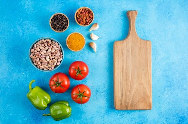 上面図。青いテーブルの上に木の板と豆と野菜とスパイス