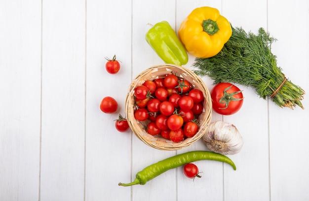 Vista superiore delle verdure come canestro del pomodoro con il bulbo dell'aglio del pepe e mazzo di pomodori di aneto intorno su superficie di legno