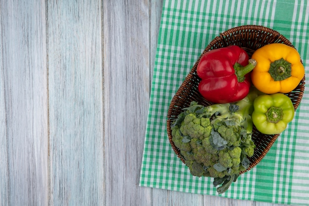 Vista dall'alto di verdure come broccoli e peperoni nel cestello sul panno plaid su sfondo di legno con spazio di copia