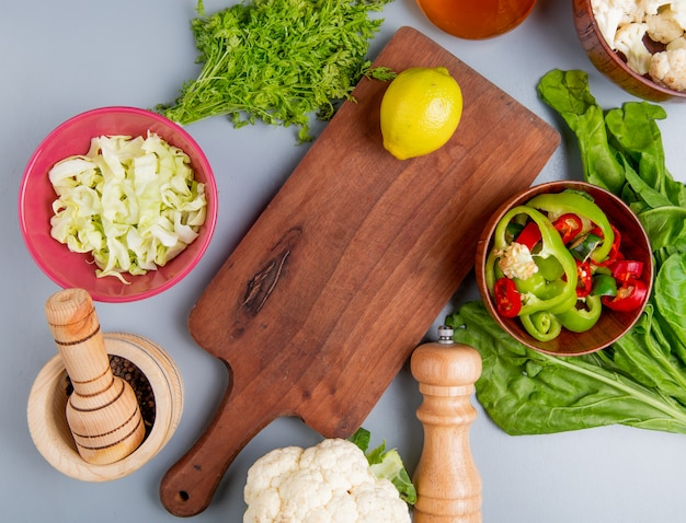 Top view of vegetables as bunch of coriander spinach sliced cabbage cauliflower sliced pepper with black pepper seeds and lemon on cutting board on blue background