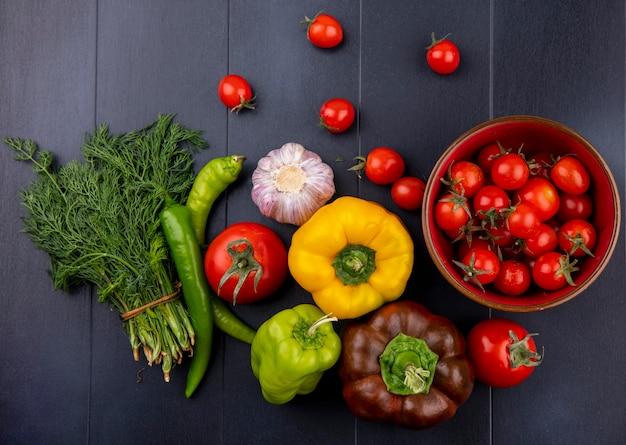Vista superiore delle verdure come mazzo di pomodoro dell'aglio del pepe dell'aneto sulla superficie del nero