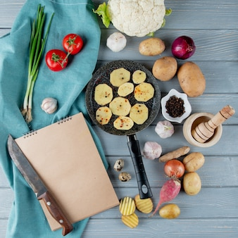 Top view of vegetables as cauliflower radish onion tomato and knife garlic crusher with pan of potato slices on wooden background