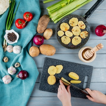 Top view of vegetables as celery tomato onion garlic egg with woman hands cutting potato on cutting board on wooden background