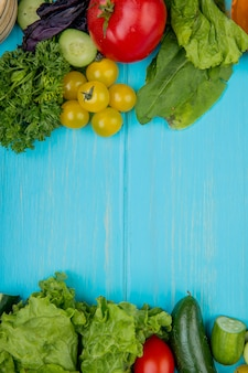 Top view of vegetables as coriander basil tomato spinach lettuce cucumber on blue with copy space