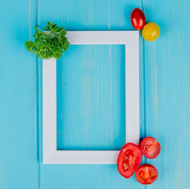 Top view of vegetables as coriander and tomatoes with white frame on blue with copy space