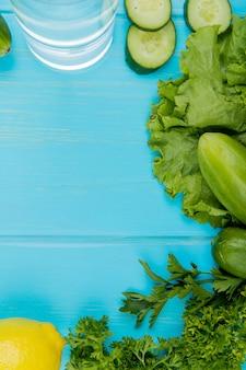 Vista superiore delle verdure come coriandolo della lattuga del cetriolo con acqua della disintossicazione e limone su superficie blu