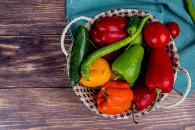 Top view of vegetables as cucumber pepper tomato in basket on blue cloth and wooden surface with copy space