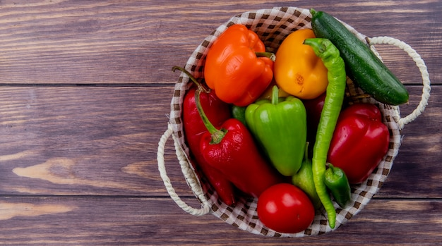 Top view of vegetables as cucumber pepper tomato in basket on wooden surface with copy space